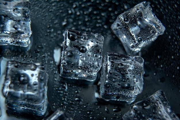 Cubos de gelo quadrados com gotas de água limpa em um fundo preto / conceito de gelo