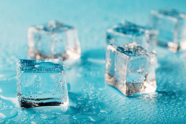 Cubos de gelo são espalhados com gotas de água espalhadas close-up.