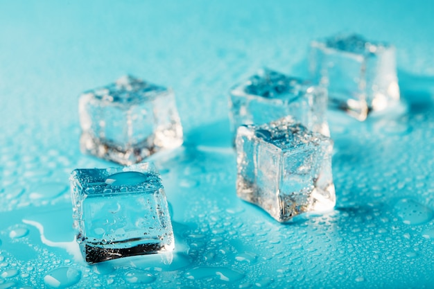 Cubos de gelo são espalhados com gotas de água espalhadas
