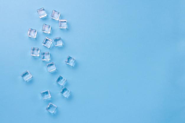 Cubos de gelo sobre um fundo azul claro. vista plana leiga, superior.