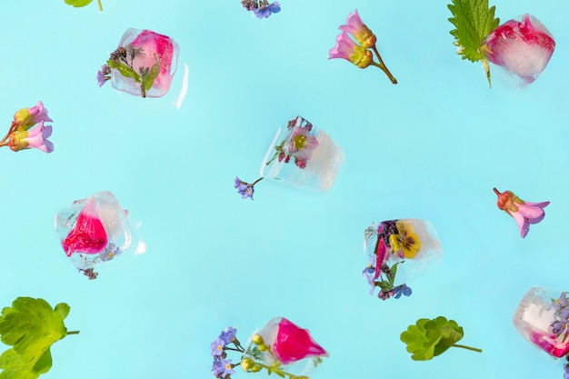 Cubos de gelo voando com flores frescas na mesa pastel.