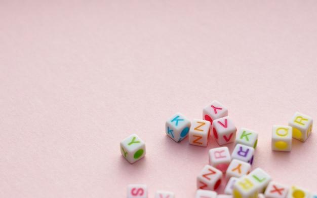 Cubos de letras do alfabeto colorido sobre fundo rosa