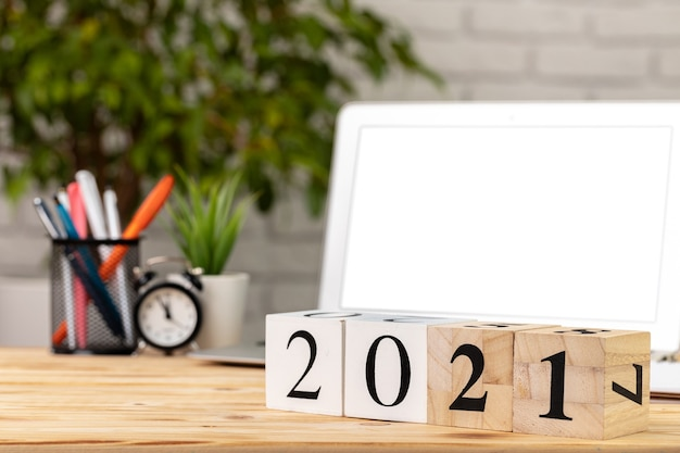 Cubos de madeira 2021 anos na mesa de trabalho com laptop aberto.