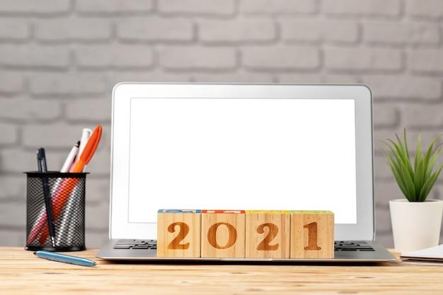 Cubos de madeira 2021 anos na mesa de trabalho com laptop aberto