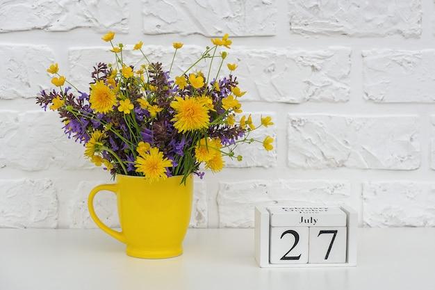 Cubos de madeira calendário 27 de julho e copo amarelo com flores coloridas brilhantes contra a parede de tijolos brancos. data do calendário do modelo