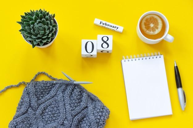 Cubos de madeira calendário 8 de fevereiro. xícara de chá com limão, bloco de notas aberto vazio para texto. vaso com tecido suculento e cinza t