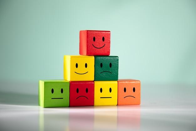 Cubos de madeira coloridos com desenhos de emoções