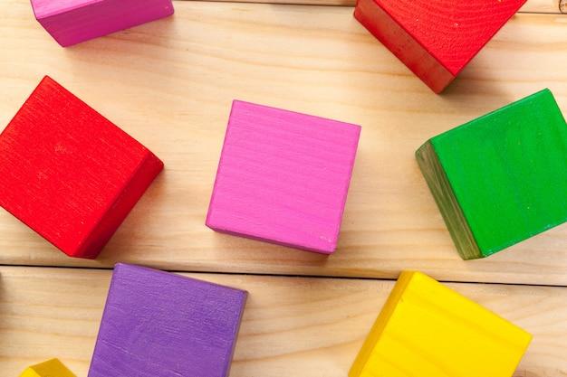 Cubos de madeira coloridos no fundo da mesa de madeira
