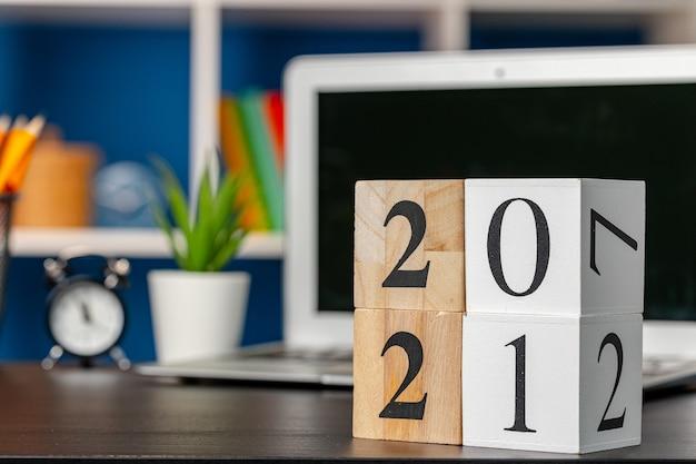 Cubos de madeira com 2021 anos na mesa de trabalho com laptop aberto