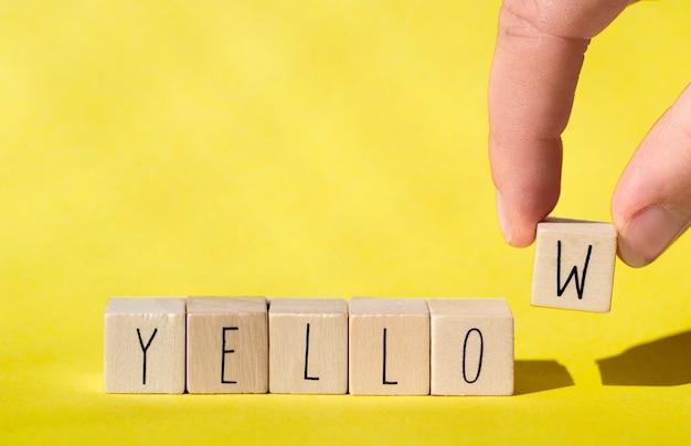Cubos de madeira com a palavra amarelo sobre fundo amarelo, conceito alegre do verão