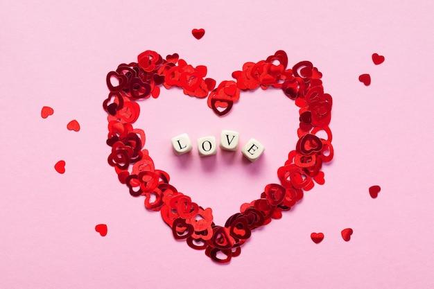 Cubos de madeira com a palavra amor no centro do coração, feitos por pequenos corações vermelhos em fundo rosa