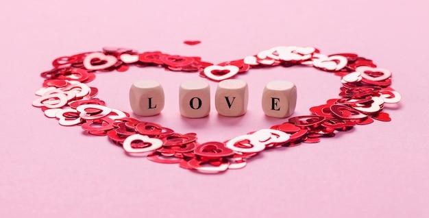Cubos de madeira com a palavra amor no centro feitos de confete em forma de coração no fundo rosa