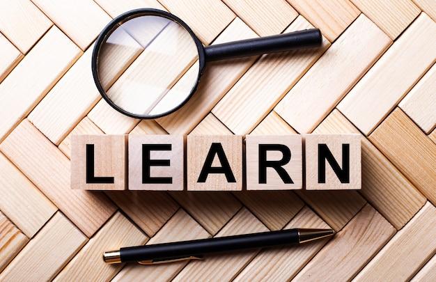 Cubos de madeira com a palavra aprender ficam sobre uma superfície de madeira entre uma lupa e uma caneta