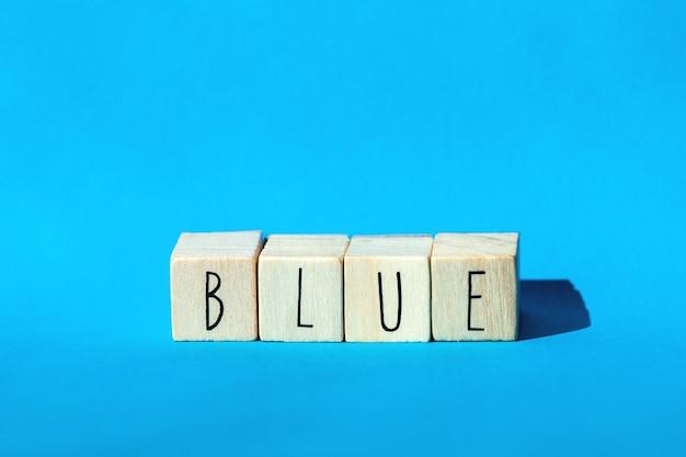 Cubos de madeira com a palavra azul com fundo azul, conceito colorido design retro