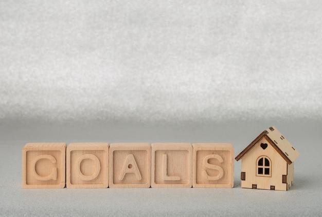 Cubos de madeira com a palavra goal e uma pequena casa de madeira em um fundo prateado. conceito de objetivo de negócios