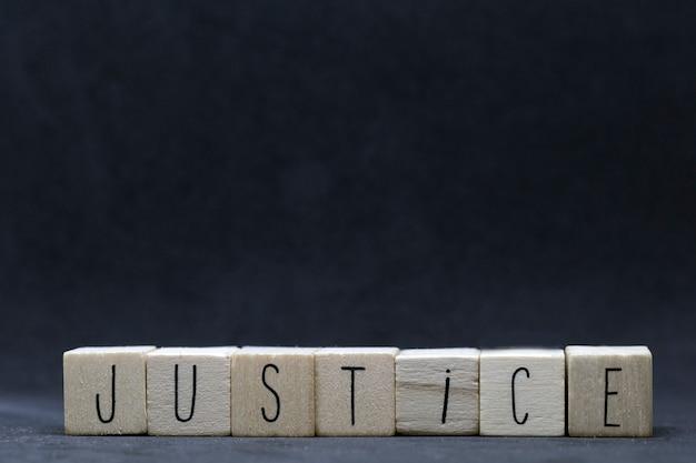 Cubos de madeira com a palavra justiça em fundo preto, vidas negras importam conceito