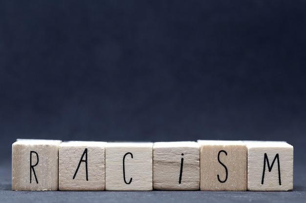 Cubos de madeira com a palavra racismo em fundo escuro, vidas negras importam conceito