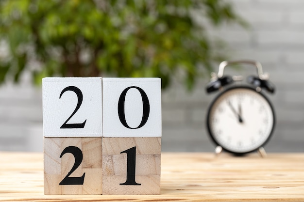 Cubos de madeira com ano 2021 e despertador na mesa de trabalho
