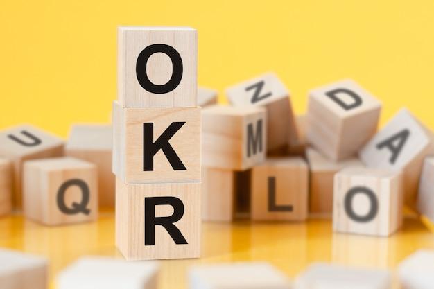 Cubos de madeira com as letras okr dispostos em uma pirâmide vertical, fundo amarelo, reflexo da superfície da mesa, conceito de negócios, okr - abreviação de objetivos e resultados-chave