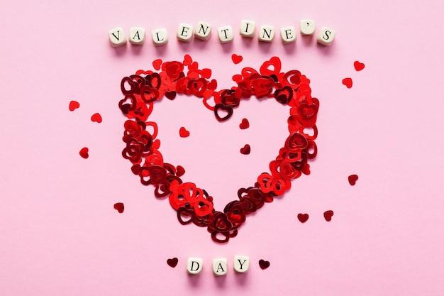 Cubos de madeira com as palavras dia dos namorados e coração feito de cor em forma de confete no fundo rosa
