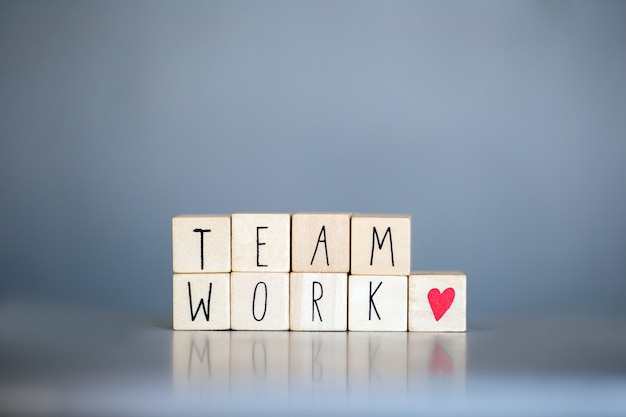 Cubos de madeira com as palavras team work para o conceito de negócio na parede azul cinza, trabalhando juntos, apoiam