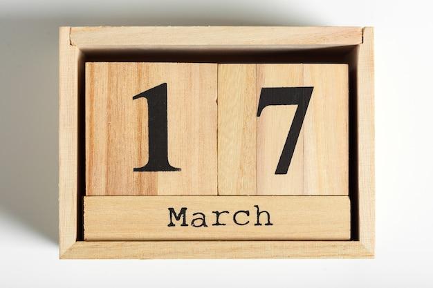 Cubos de madeira com data em fundo branco. 17 de março