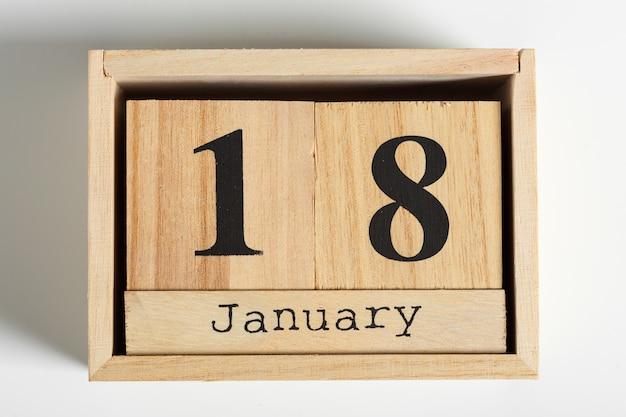 Cubos de madeira com data em fundo branco. 18 de janeiro