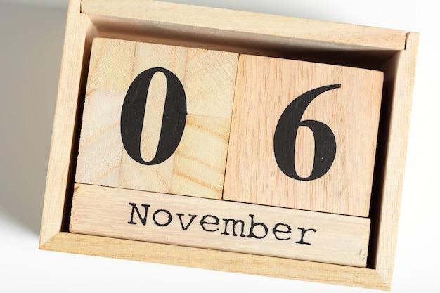 Cubos de madeira com data em fundo branco. 6 de novembro