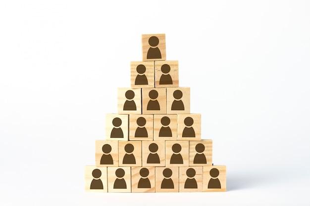 Cubos de madeira com homens alinhados com uma pirâmide sobre um fundo branco claro. conceito de corporação, pirâmide financeira, liderança, equipe unida