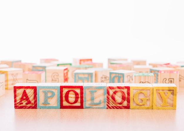 Cubos de madeira com inscrição de pedido de desculpas