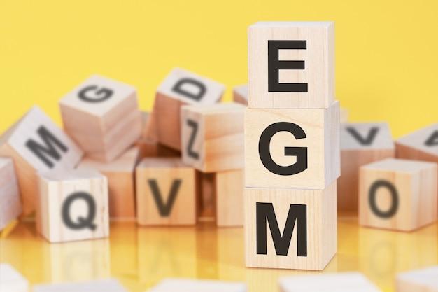 Cubos de madeira com letras egm dispostos em uma pirâmide vertical, fundo amarelo, reflexo da superfície da mesa, conceito de negócio. egm - abreviação de assembleia geral extraordinária.