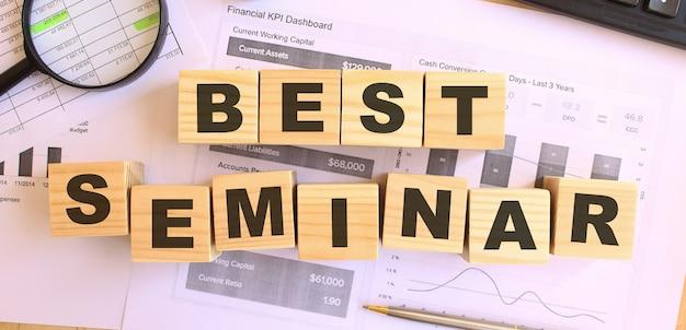 Cubos de madeira com letras em cima da mesa do escritório. texto melhor seminário. conceito financeiro.