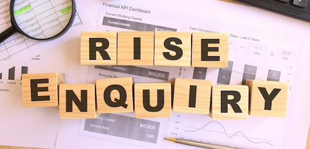 Cubos de madeira com letras em cima da mesa do escritório. texto rise inquiry. conceito financeiro.