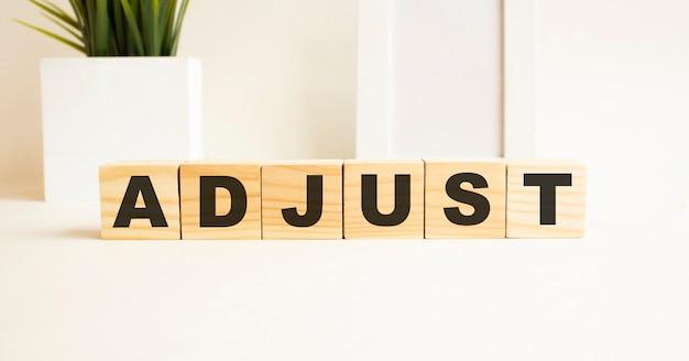 Cubos de madeira com letras em uma mesa branca. a palavra é ajuste. fundo branco com moldura, planta de casa.