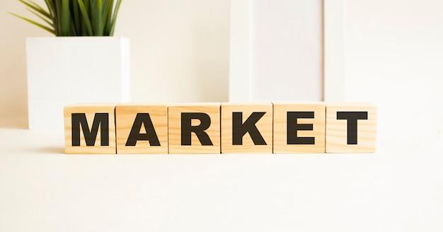 Cubos de madeira com letras em uma mesa branca. a palavra é mercado