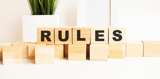 Cubos de madeira com letras em uma mesa branca. a palavra é regras. fundo branco com moldura, planta de casa.