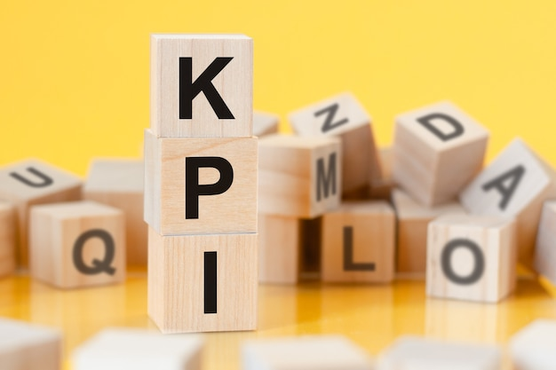 Cubos de madeira com letras kpi dispostos em uma pirâmide vertical, fundo amarelo, reflexo da superfície da mesa, conceito de negócio. kpi - abreviação de indicadores-chave de desempenho