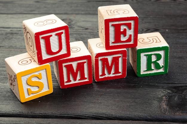 Cubos de madeira com letras na mesa de madeira, palavra de verão