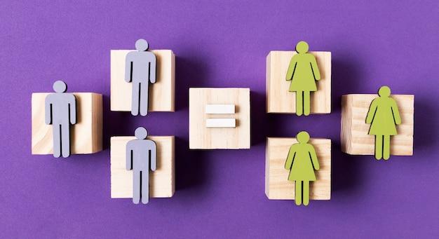 Cubos de madeira com mulheres verdes e homens azuis estatuetas igualdade conceito vista superior