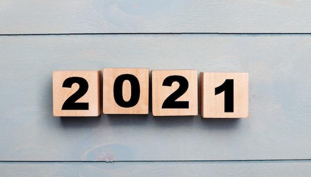 Cubos de madeira com números 2021 em um fundo de madeira azul claro. conceito de ano novo