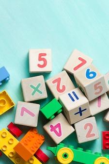 Cubos de madeira com números e tijolos de brinquedo coloridos sobre fundo de madeira turquesa.