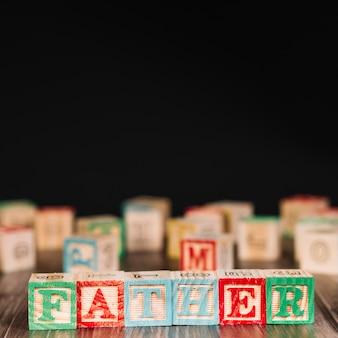 Cubos de madeira com o título do pai