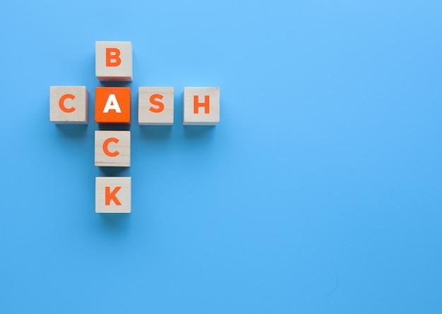 Cubos de madeira com palavras cruzadas de dinheiro de volta sobre fundo azul. dinheiro, conceito de negócio de impostos.