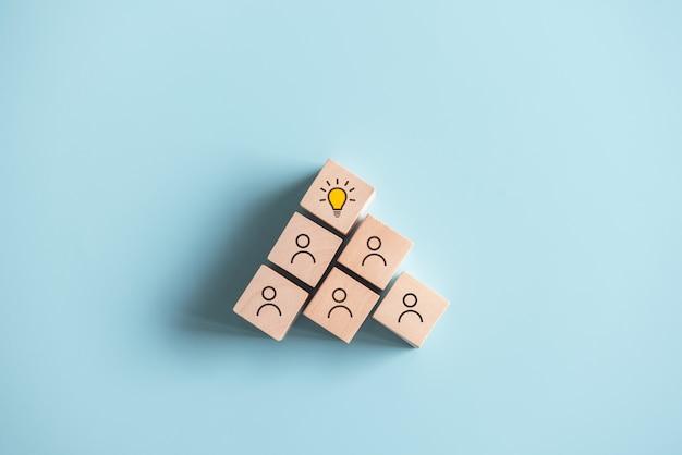 Cubos de madeira com símbolo de ideia nos ícones de pessoas