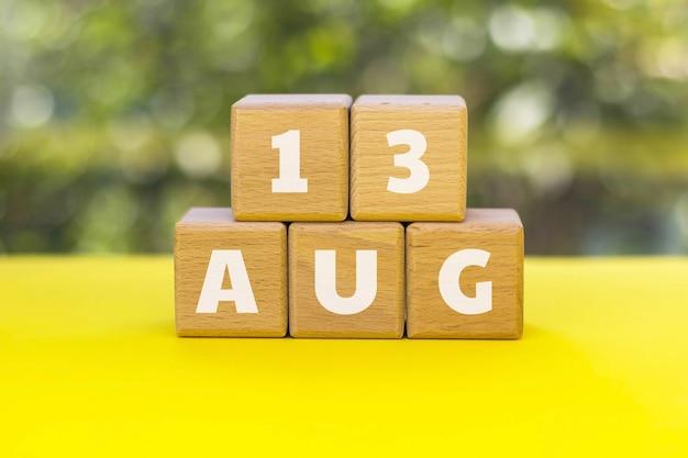 Cubos de madeira com texto 13 de agosto. 13 de agosto - dia internacional dos canhotos.