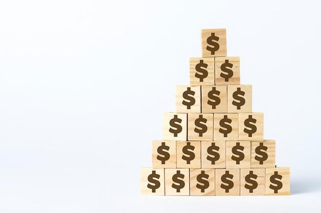 Cubos de madeira com um cifrão alinhados com uma pirâmide em um fundo branco. conceito de corporação, pirâmide financeira, liderança, equipe única, fraude, decepção