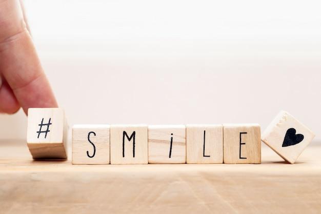 Cubos de madeira com um hashtag e a palavra sorriam, conceito de mídia social