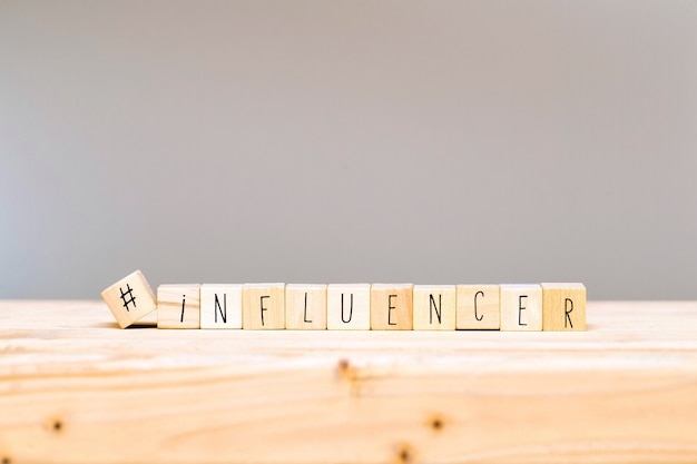 Cubos de madeira com uma hashtag e a palavra influenciador