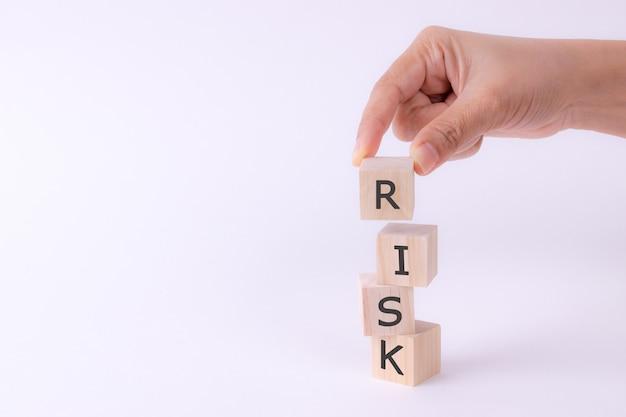 Cubos de madeira da preensão da mão com palavra do risco.