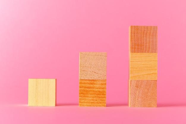 Cubos de madeira de brinquedo com espaço de cópia contra um fundo rosa close-up